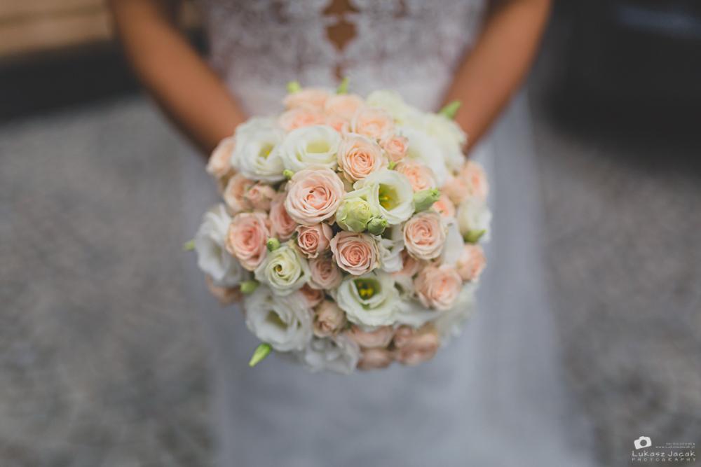 Bukiet ślubny. Panna młoda trzymająca w dłoniach ślubny bukiet kwiatów.