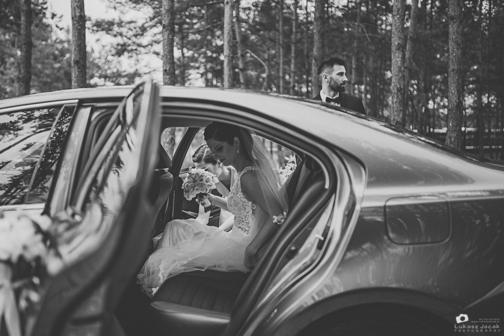 Panna młoda wsiadająca do auta, którym udali się na ślub kościelny.