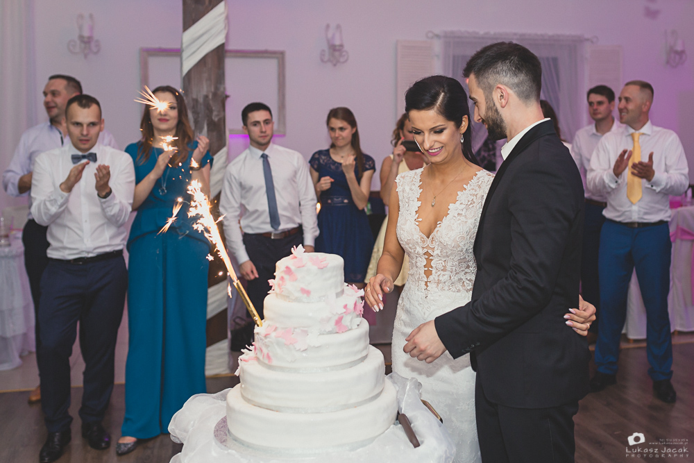 Tort weselny. Państwo Młodzi kroją tort. Reportaż śluby w Otwocku.